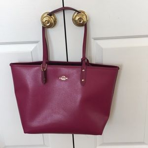 Berry colored large reversible Coach bag.